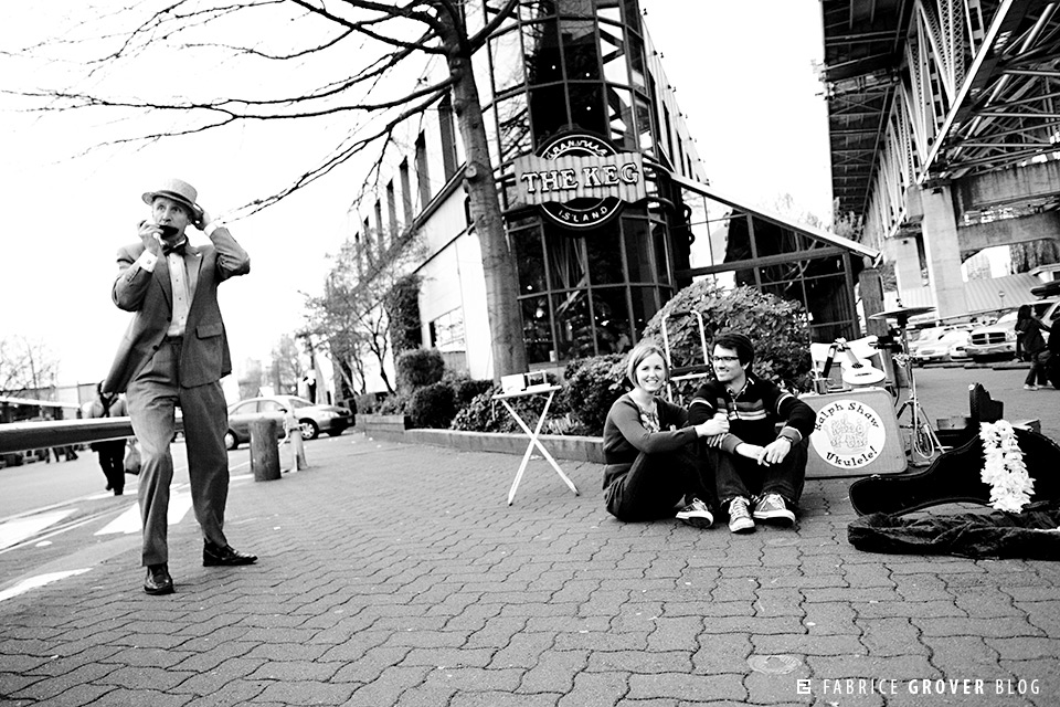 Couple watch Ralph Shaw Ukelele on Granville Island in front of The Keg in Vancouver BC
