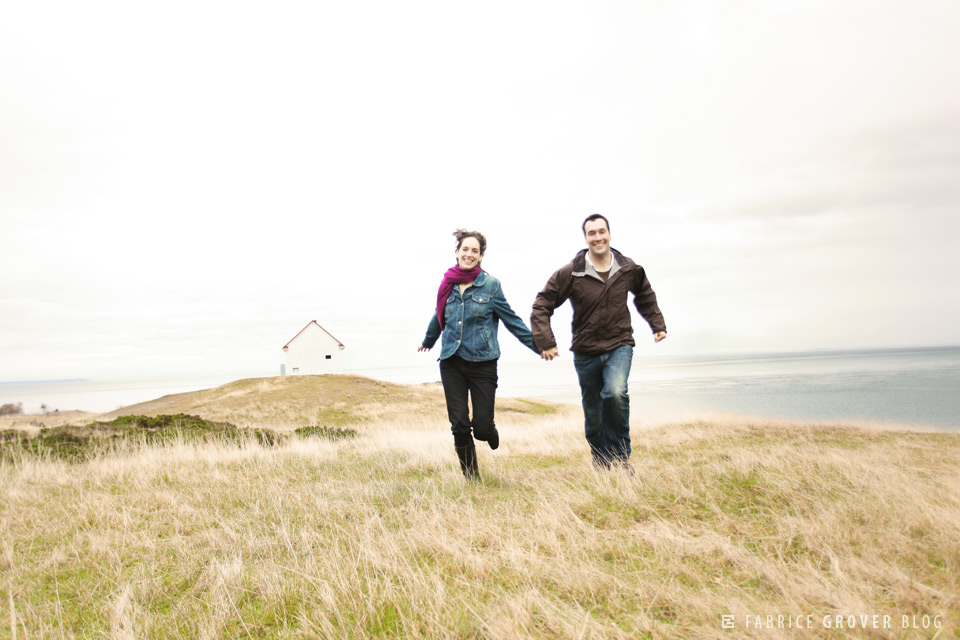 A couple runs by East Point Lighthouse on Saturna Island engagement shoot