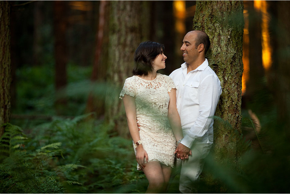 engagement photos stanley park: couple relaxes amidst trees in forest of Stanley Park
