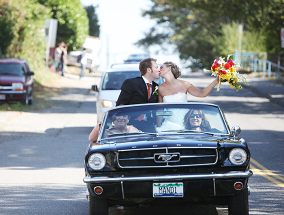 vancouver wedding photographer image of newlyweds kissing in their vintage car in White Rock BC