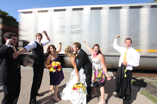 vancouver wedding photographer party cheers as couple kiss in front of moving train White Rock BC