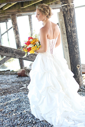 vancouver wedding photographer bride holds bouquet of flowers on the beach in White Rock BC Canada