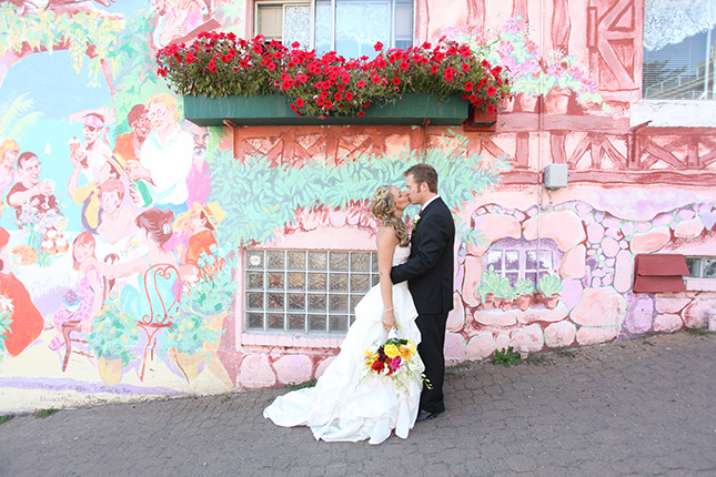 vancouver wedding photographer bride and groom kiss under red geraniums in White Rock BC