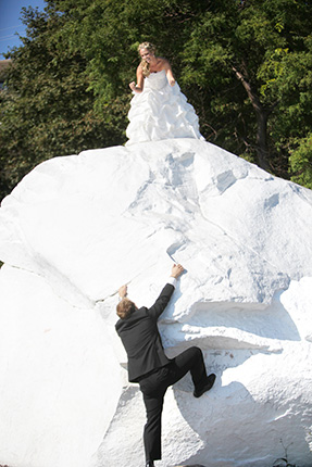 vancouver wedding photographer groom climbs the white rock while his braid encourages him