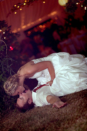 vancouver wedding photographer couple kisses in grass at reception on farm in white rock bc