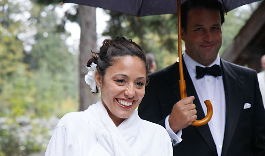 bride smiles under grooms umbrella for rainy vancouver wedding photography in Whistler BC